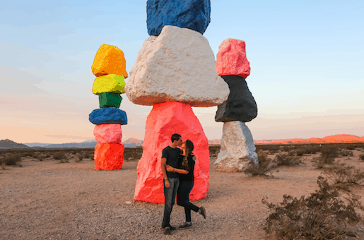 Couple kissing at the 7 magic Mountains in Las Vegas during sunrise.