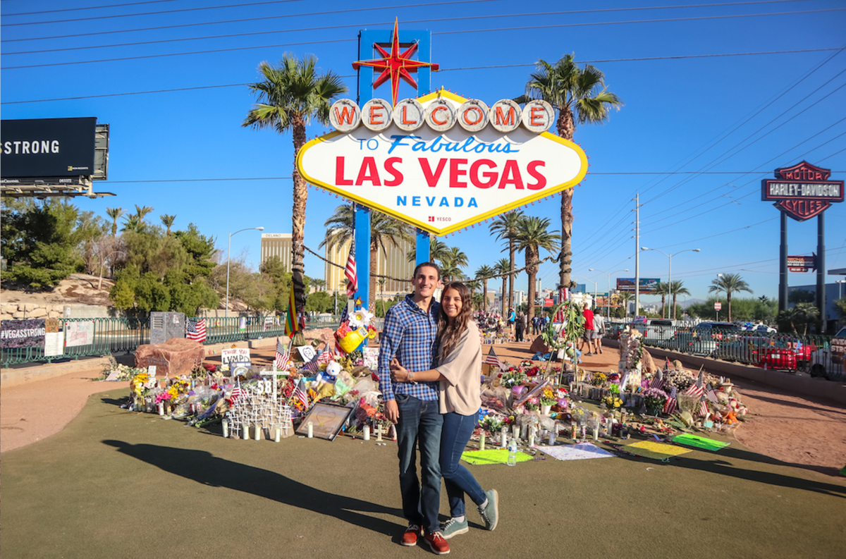 """Couple smiling at the famous """"Welcome to Fabulous Las Vegas"""" sign."""