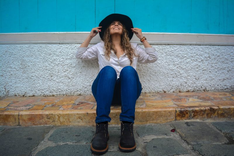 Girl sitting on the street wearing hat and shoes