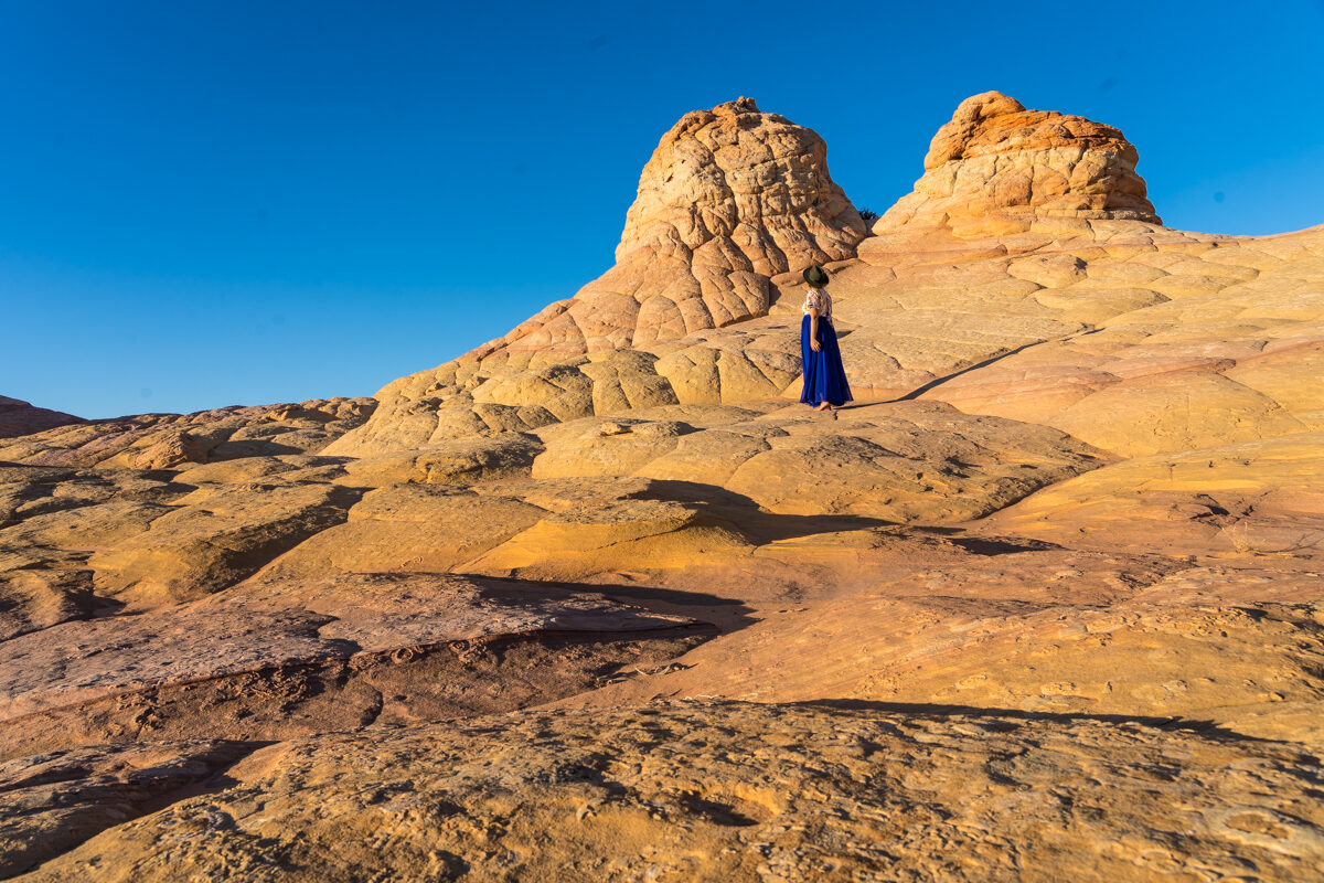 Girl on a blue skirt witnessing beautiful rock formations in utah during sunset