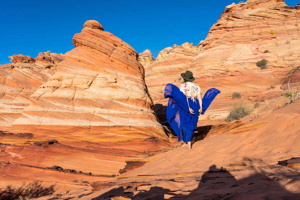 Girl on a blue skirt witnessing beautiful rock formations in utah