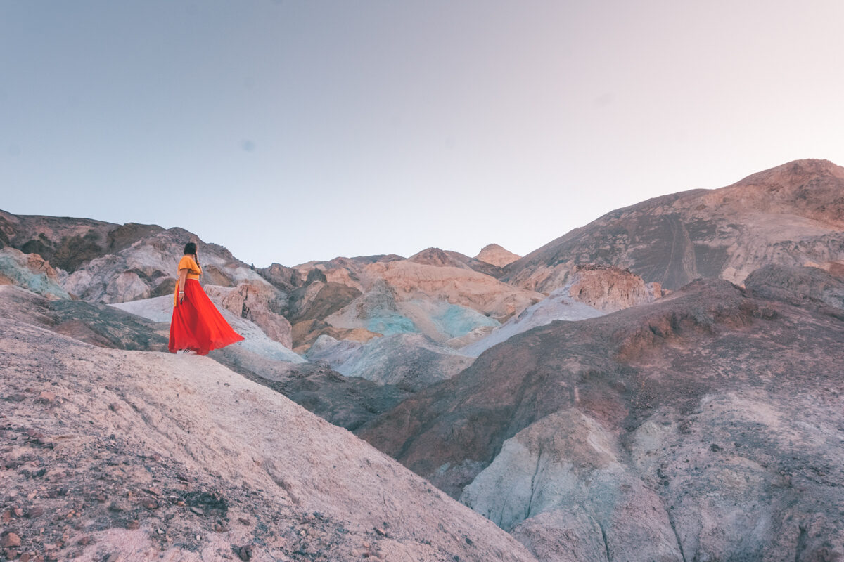Girl dancing at the colorful mountains in Death Valley National Park in California.