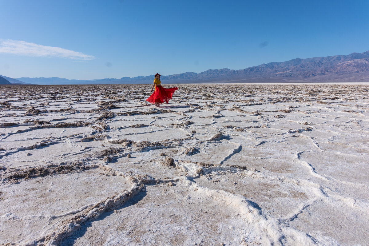 Girl dancing at the salt flats in Death Valley National Park in California.