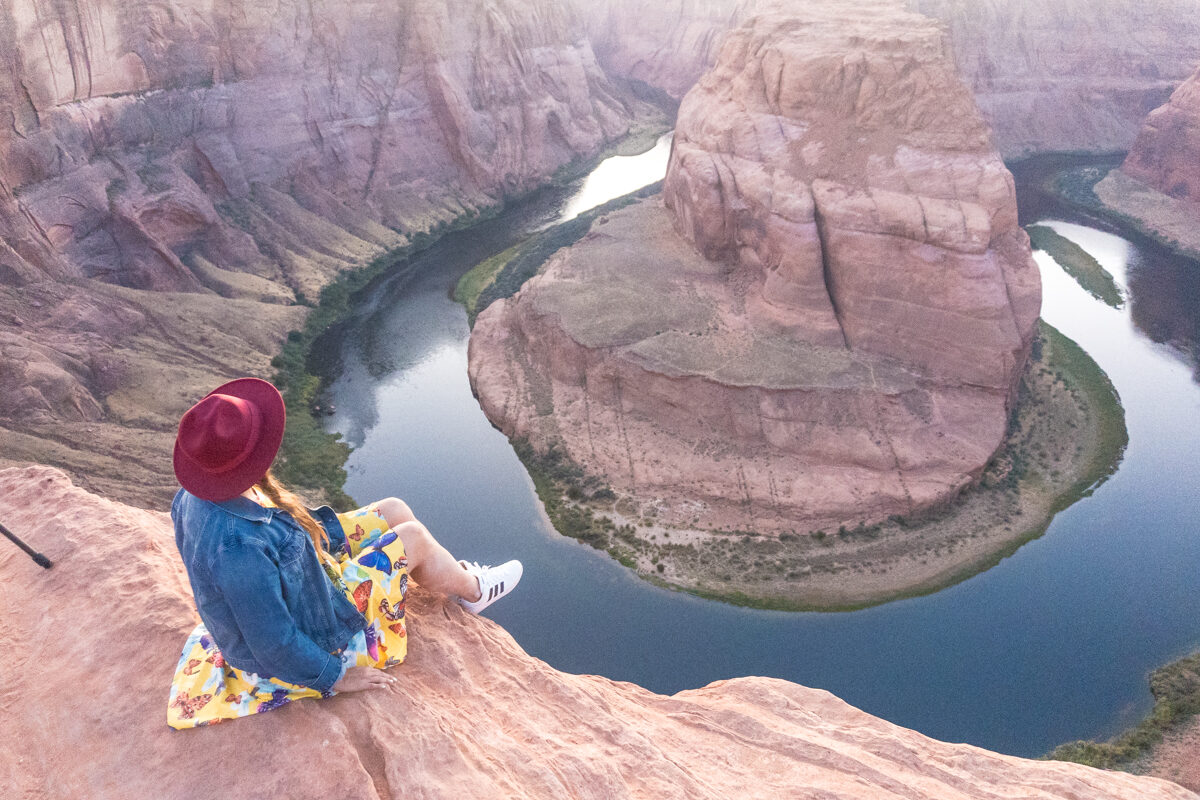 Girl wearing a red hat and yellow dress watching sunset at the Horseshoe bend in Arizona
