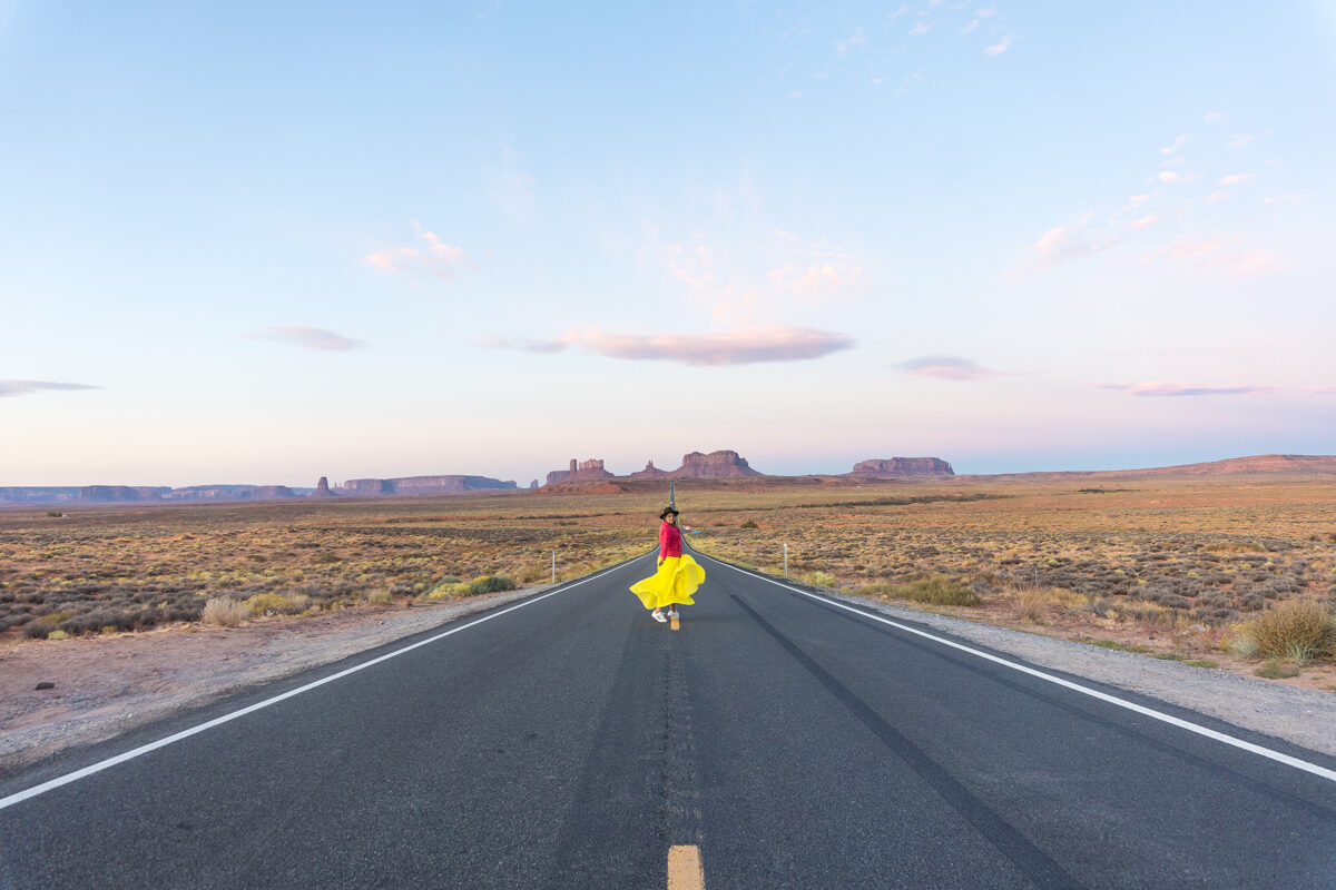 Girl walking in the middle of the street wearing a yellow skirt at Monument Valley in Utah for sunrise