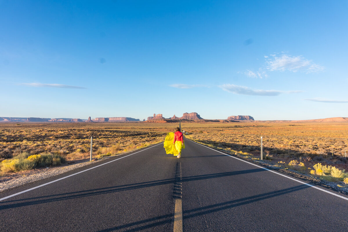 Girl walking in the middle of the street wearing a yellow skirt at Monument Valley in Utah